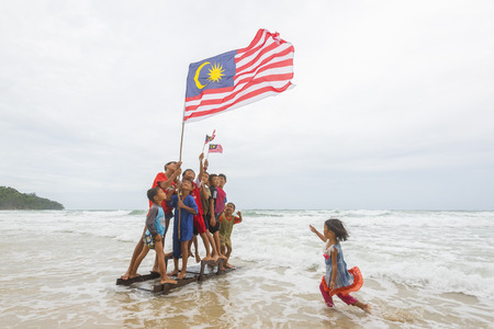 KUDAT SABAH, MALAYSIA - 6th AUGUST 2016 ; Independence Day / Merdeka day concept - Happy kids playing and hold a Malaysian flag on beach