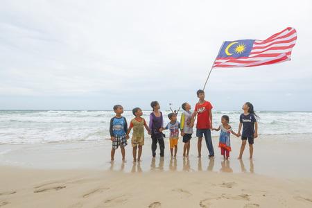 クダット マレーシア ・ サバ州 2016 年 8 月 6 日;独立記念日・ ムルデカ日コンセプト - ローカル子供の歌とホールドのビーチにマレーシア国旗 写真素材 - 65469624