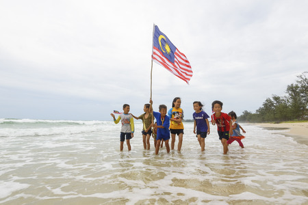 KUDAT SABAH, MALAYSIA - 31st AUGUST 2016 ; Independence Day / Merdeka day concept - The local kids holding a Malaysian flag running on beach