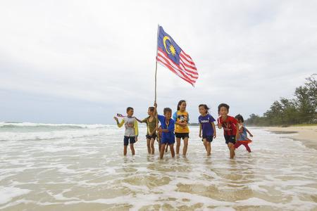クダット マレーシア ・ サバ州 2016 年 8 月 31 日;独立記念日・ ムルデカ日コンセプト - ローカル子供のビーチを走るマレーシアのフラグを保持して