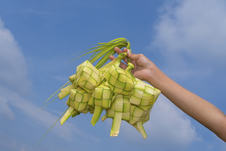 A hand holding Ketupat - Malay cuisine made from glutinous rice packed inside a diamond shaped container of wooven palm leaf with blue sky