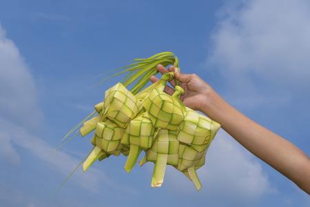 菱形の青い空とヤシの葉を手織りのコンテナー詰め込んだ Ketupat - もち米から作られたマレー料理を持つ手 写真素材