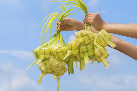 A hand holding Ketupat - Malay cuisine made from glutinous rice packed inside a diamond shaped container of wooven palm leaf.