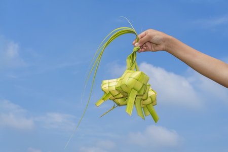 diamond shaped: A hand holding Ketupat - Malay cuisine made from glutinous rice packed inside a diamond shaped container of wooven palm leaf.