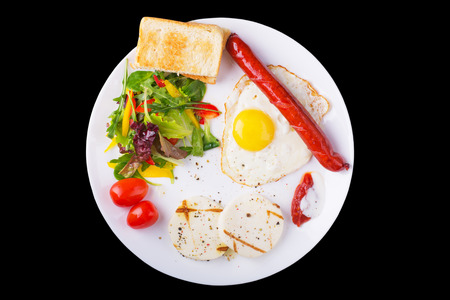 Fried egg and sausage on the plate with green salad and cheese photo