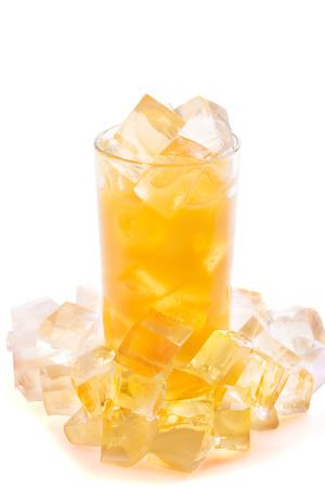 Full glass of orange juice with ice on white background