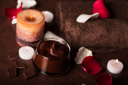 body scrub: SPA concept: chocolate mudpack, rose petals, candle and towels Stock Photo