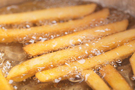 quick snack: French fries in hot fat (close up shot)
