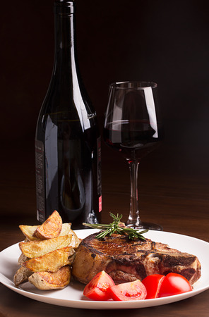 carnes rojas: Carne a la brasa con verduras, hierbas y vino tinto en la mesa Foto de archivo