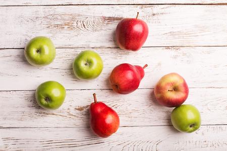 pera: Manzanas y peras en el fondo de madera blanca