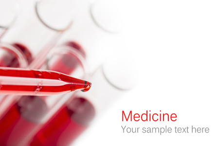 Pipette with drop of blood and test tubes 스톡 콘텐츠