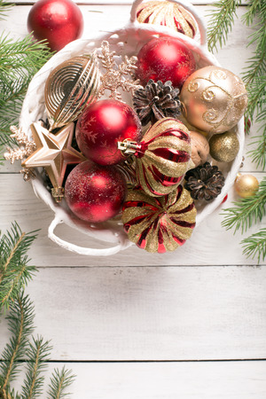Christmas basket with red and golden ornaments, fir-cones on a wooden table