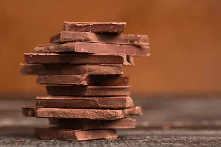 cope: Pile of dark chocolate on a wooden table (with cope space) Stock Photo