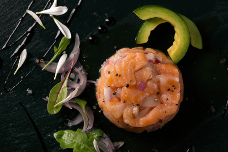 a portion: Tartare with salmon and onion on the plate with salad
