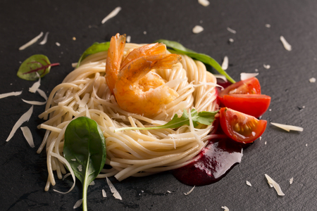 parmezan: Spaghetti with shrips and parmezan on the black plate Stock Photo