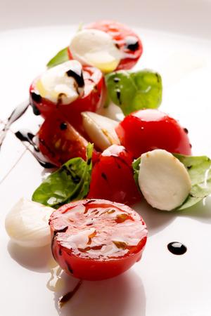 ensalada: Ensalada Caprese con mozzarella, tomate y albahaca en la placa blanca
