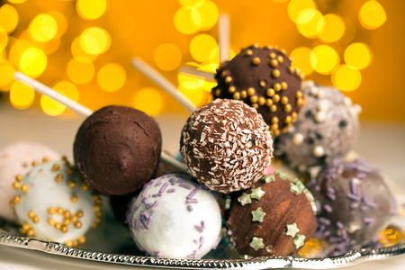 chocolate balls: Colorful cake pops on the blurred yellow bokeh background