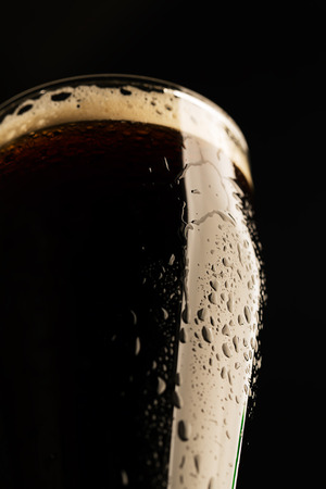 Glass of porter beer with drops of beer on the surface