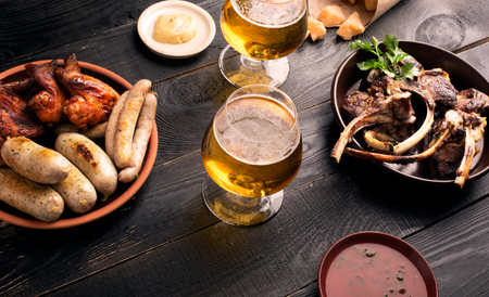 ipa: Two glasses of beer on the black table with snacks