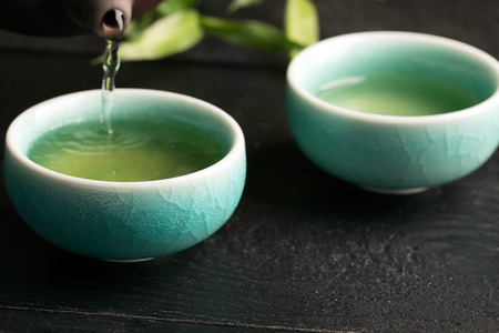 アジアの粘土のティーポットとガラス張りの素焼鉢の緑茶