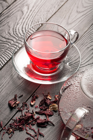 flowers black background: Hibiscus tea in the cup and teapot on a wooden background Stock Photo