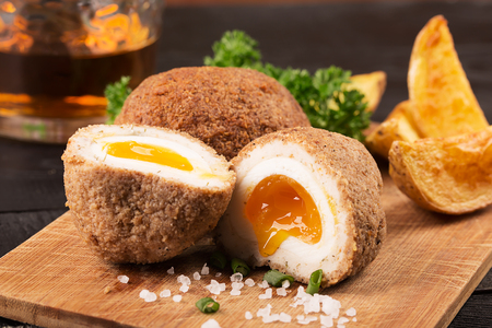 Traditional scotch eggs on a wooden plate Stock Photo