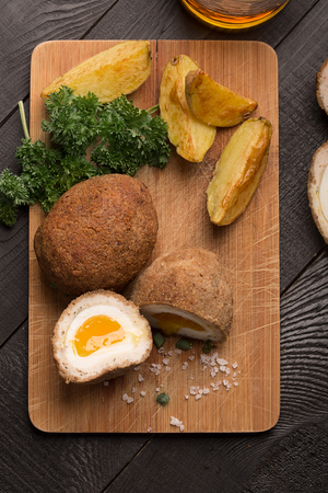 scotch: Traditional scotch eggs on a wooden plate Stock Photo