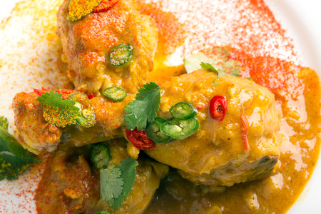 thighs: Delicious chicken thighs with curry sauce and chili Stock Photo
