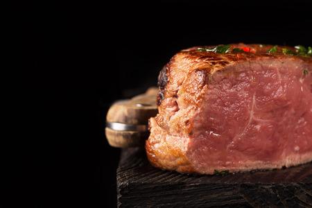 medium close up: Grilled Steak Meat on the wooden surface. Dark background