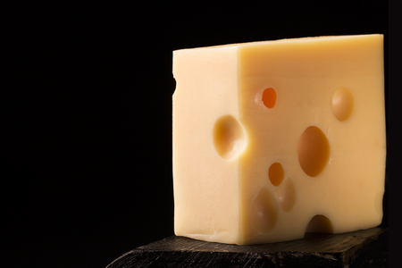 emmental: Piece of emmental cheese on a wooden surface. Dark background