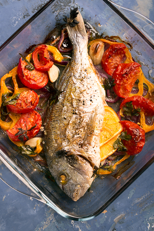 Uncooked dorado or sea bass fish with vegetables, herbs and spices