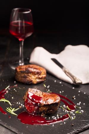 medium close up: Grilled steak meat (mignon) on the dark surface. Dark background