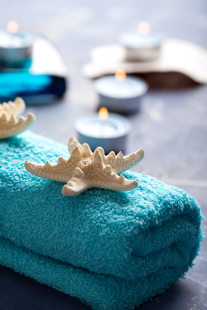 SPA still life with towel, candles and starfish on blue surface Stock Photo