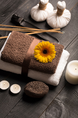 vertical wellness: SPA still life with towel, candles and gerbera flowers on a black wooden surface