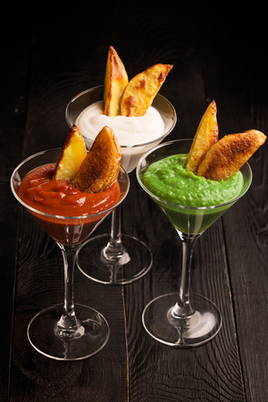 Fried potatoes with sauces (ketchup, pesto and yoghurt)