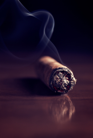 Fuming Havana cigar on a wooden table (with copy space) Stock Photo