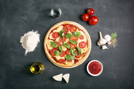 Pizza (margherita) and ingredients on the black chalkboard