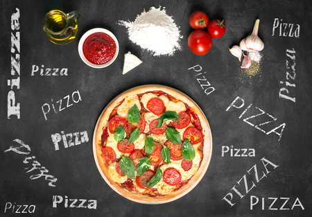 Ingredients of pizza on the chalkboard (tomatoes, cheese, sauce, water, spices, oil and flour). Prepared pizza. Inscriptions on the board
