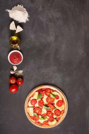 (トマト、チーズ、ソース、水、香辛料、油、小麦粉) 黒板にピザの材料。それはあなたのテキストや画像の空間です 写真素材