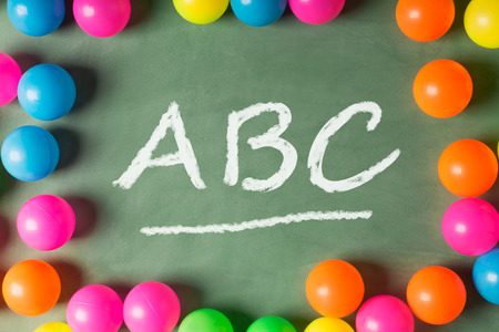 describe: ABC (letters) on the green chalkboard. Top view. Image could be used to advertise or describe learning process or school subject (for example, English) Stock Photo
