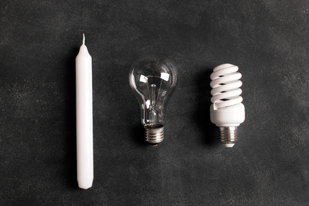 describing: White candle and electric bulbs on the black chalkboard. Concept describing the evolution of lighting Stock Photo
