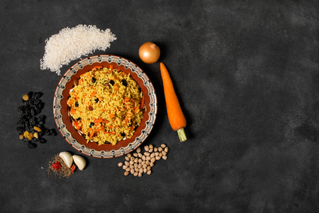 Plate of oriental pilaf with rice and vegetables on the black background with copy space