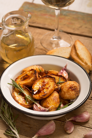 vertical orientation: Baked potato with rosemary and garlic on the rustic table (vertical orientation) Stock Photo