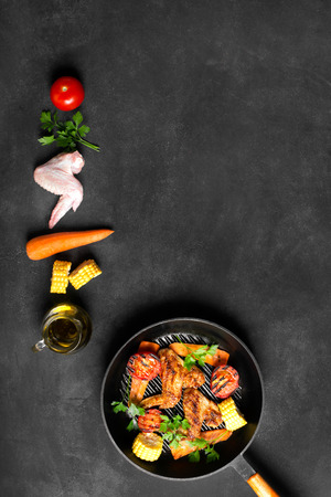 vertical orientation: Chicken wings cooked on the grill  pan with corn and tomatoes on the black chalkboard (vertical orientation) Stock Photo