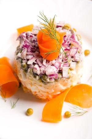 ensaladilla rusa: Olivie tradicional ensalada rusa con verduras cocidas y mayonesa sobre un fondo blanco