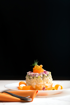 Traditional Russian salad olivie with boiled vegetables and mayonnaise on a black background