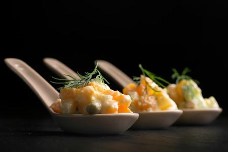 ensaladilla rusa: Olivie tradicional ensalada rusa con verduras cocidas y mayonesa sobre un fondo negro. cuchara de Control de Porciones