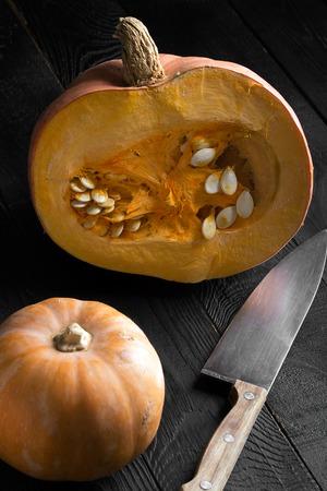 vertical orientation: Raw pumpkins on the black wooden background. Vertical orientation