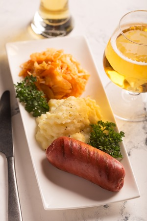Grilled sausages, mashed potatoes and stewed cabbage with glass of beer on the table. Side view, white background
