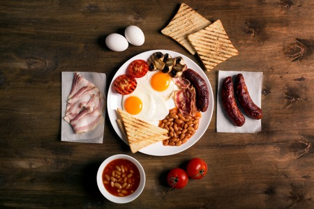 English breakfast prepared with two fried eggs, beans in tomato sauce, grilled tomatoes, mushrooms, bacon and toasts. Meal on a rustic wooden table